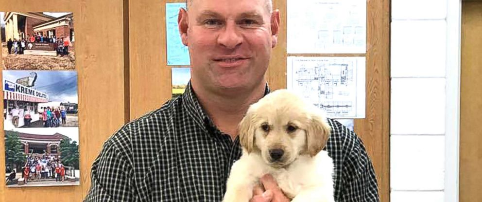 PHOTO: Troy Rogers, a teacher, poses with the puppy that was a gift from his high school students.