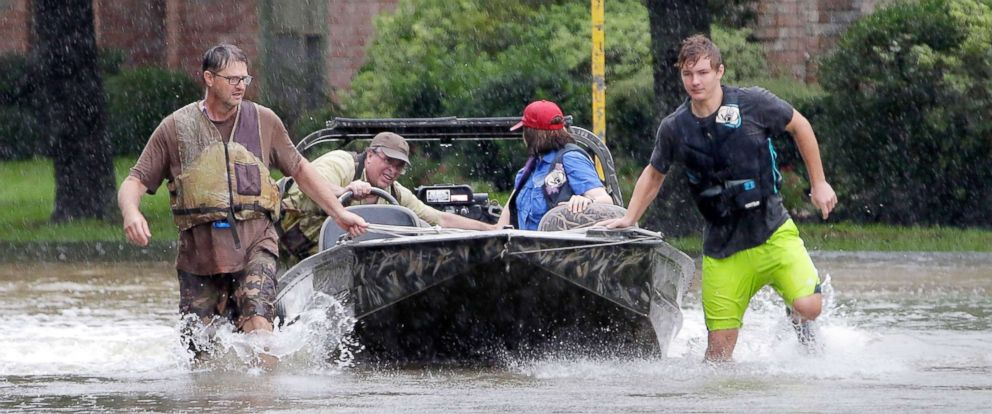 PHOTO: Volunteers push their boat along flooded streets as they look for stranded residents in Klein, a north suburb of Houston, Texas, Aug. 28, 2017.