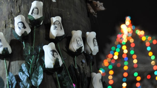PHOTO: Roses printed with the faces of the victims are placed at a memorial around a Christmas tree in the center of Sandy Hook, Conn.