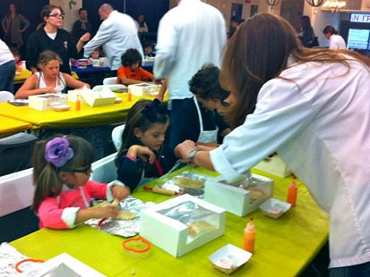 PHOTO: Chef Karen assists children at the Cookie Baking and Decorating event.
