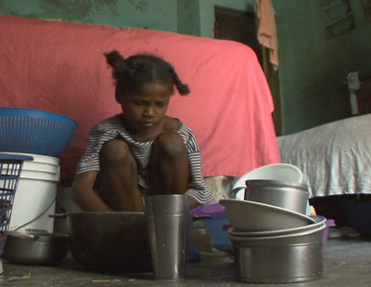Restavek Child Scrubs Pots In Haiti