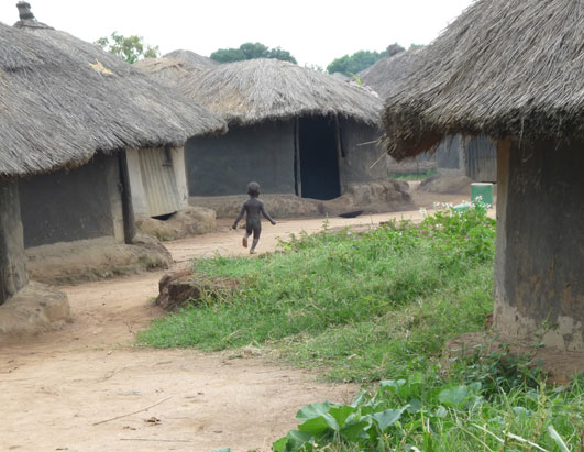 Here, a naked child runs between the thatched huts. Many of these tiny huts hold large and growing families.