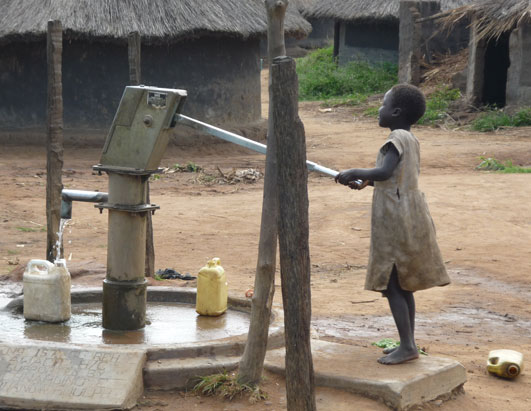 As part of her chores, this girl pumps water from a well inside Awach.