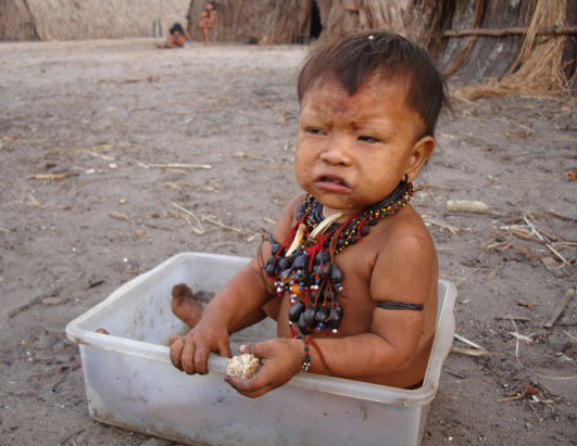 A female toddler, wearing traditional jewelry and eating yucca bread.