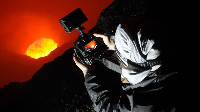 PHOTO: ABC News Asia Producer Karson Yiu lies right on the edge of Mt. Marum's crater.