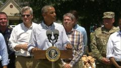 The president toured a flooded neighborhood before pledging federal assistance.