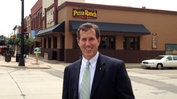 Rick Santorum poses in front of a Pizza Ranch franchise in Le Mars, Iowa, Aug. 2013.