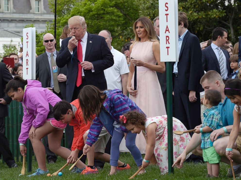 PHOTO: President Donald Trump, accompanied by first lady Melania Trump, blows a whistle to begin an Easter Egg Roll race on the South Lawn of the White House in Washington, April 17, 2017, during the annual White House Easter Egg Roll.