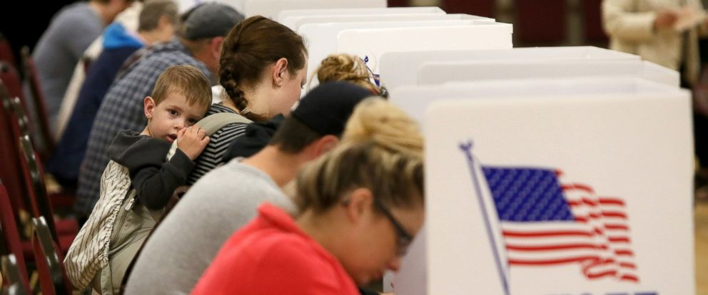 PHOTO: A child sits in a backpack child carrier as voters fill out their ballots at a polling station at the Mt. Zion Missionary Baptist Church, Nov. 8, 2016, in St. Charles, Mo.