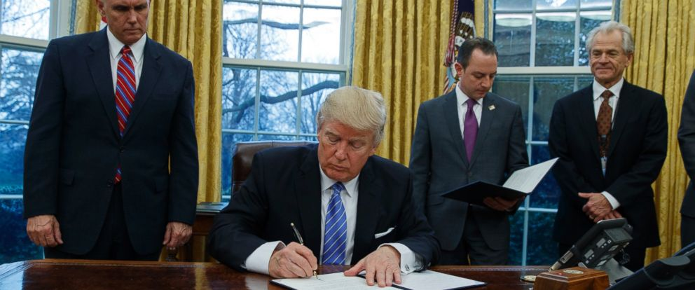 PHOTO: President Donald Trump signs an executive order to withdraw the U.S. from the 12-nation Trans-Pacific Partnership trade pact agreed to under the Obama administration, Jan. 23, 2017, in the Oval Office of the White House in Washington.