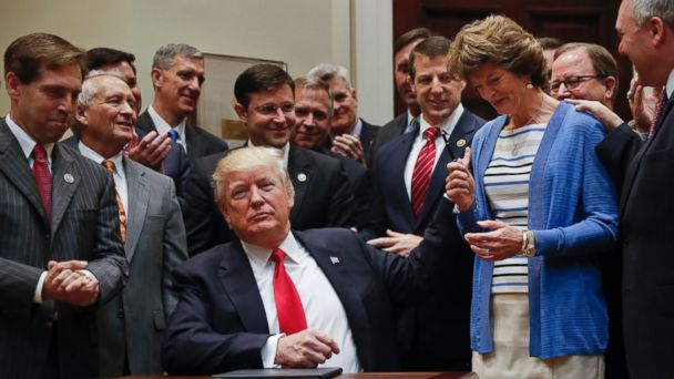 PHOTO: President Donald Trump gives the pen he used to sign an Executive Order to Sen. Lisa Murkowski, R-Alaska, right, in the Roosevelt Room of the White House in Washington, April 28, 2017.