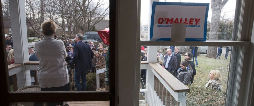 PHOTO: Judy Anderson, left, watches as Democratic presidential candidate, former Maryland Gov. Martin OMalley, center, speaks to voters outside the her home on Jan. 31, 2016 in Johnston, Iowa.