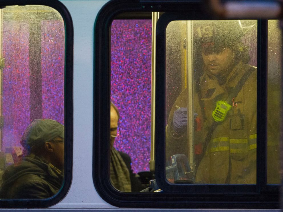PHOTO: A firefighter attends people on a bus to assess triage needs after people were evacuated from a smoke filled Metro subway tunnel in Washington, Jan. 12, 2015.