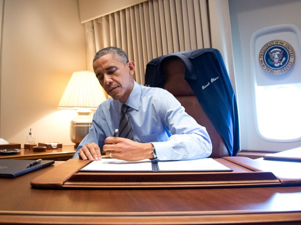 PHOTO: President Barack Obama signs two presidential memoranda associated with his actions on immigration in his office on Air Force One as he arrives at McCarran International Airport in Las Vegas on Nov. 21, 2014.