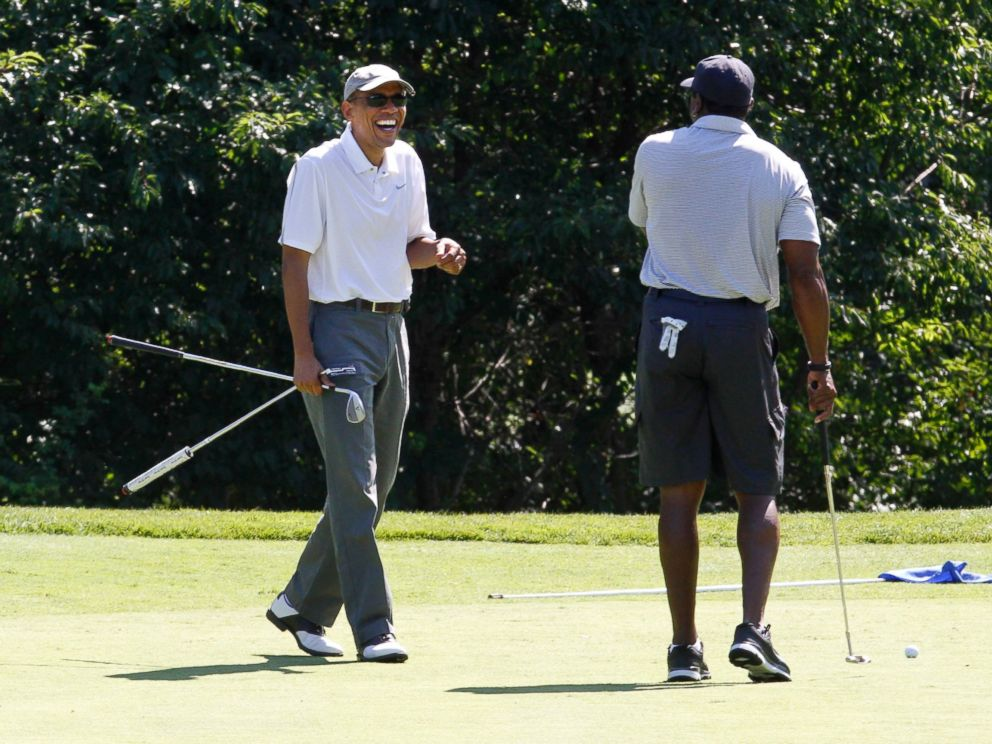 PHOTO: President Barack Obama laughs while golfing with former NFL player Ahmad Rashad at Farm Neck Golf Club in Oak Bluffs, Mass., on the island of Marthas Vineyard, Aug. 9, 2014.