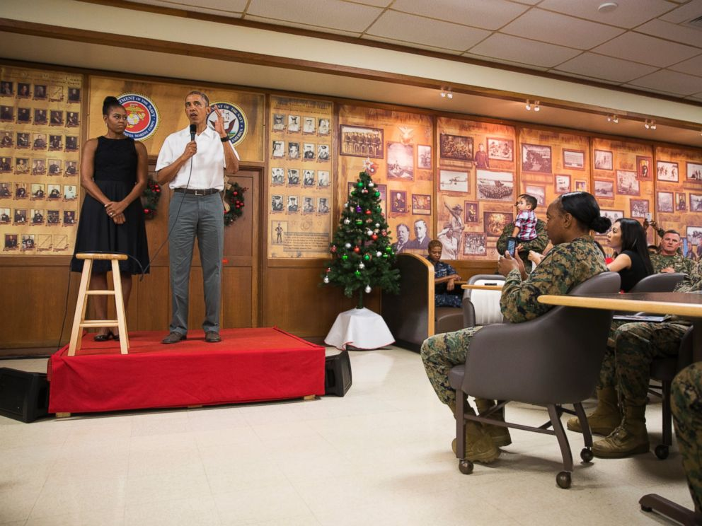 PHOTO: First lady Michelle Obama, left, looks on as President Barack Obama speaks during an event to thank service members and their families at Marine Corp Base Hawaii, on Friday, Dec. 25, 2015, in Kaneohe Bay, Hawaii.
