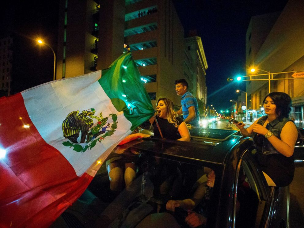 PHOTO: A woman waves the Mexican flag while driving past the Albuquerque Convention Center after a rally by Republican presidential candidate Donald Trump, May 24, 2016, in Albuquerque, N.M.