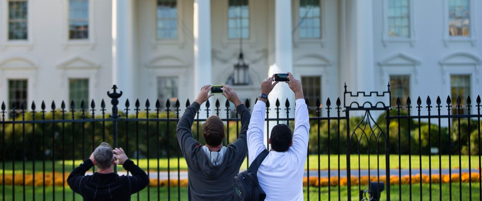 PHOTO: Visitors take photos of the White House on the sidewalk in front of the White House in Washington, Oct. 23, 2014.