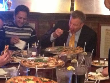 PHOTO: New York City Mayor Bill de Blasio, center, uses a knife and fork to pizza at Goodfellas Pizza in the Staten Island borough of New York on Jan. 10, 2014.