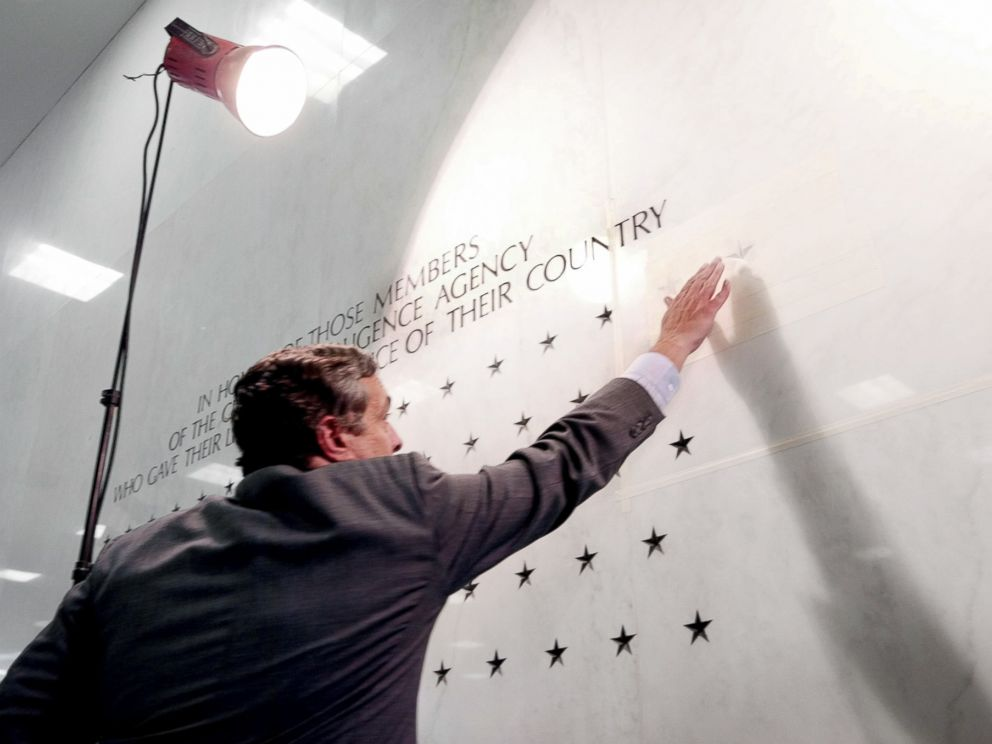 PHOTO: Former Director of the Central Intelligence Agency George Tenet reaches out to touch a five-pointed star freshly carved into the marble-faced lobby wall of CIA headquarters in Langley, Va., May 23, 2002.