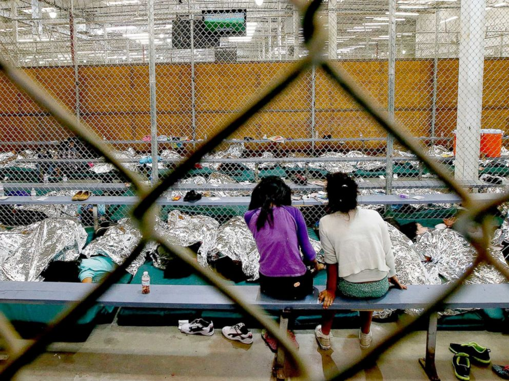 PHOTO: Two young girls watch a World Cup soccer from their holding area where hundreds of immigrant children are being processed at the U.S. Customs and Border Protection Nogales Placement Center, June 18, 2014, in Nogales, Ariz.