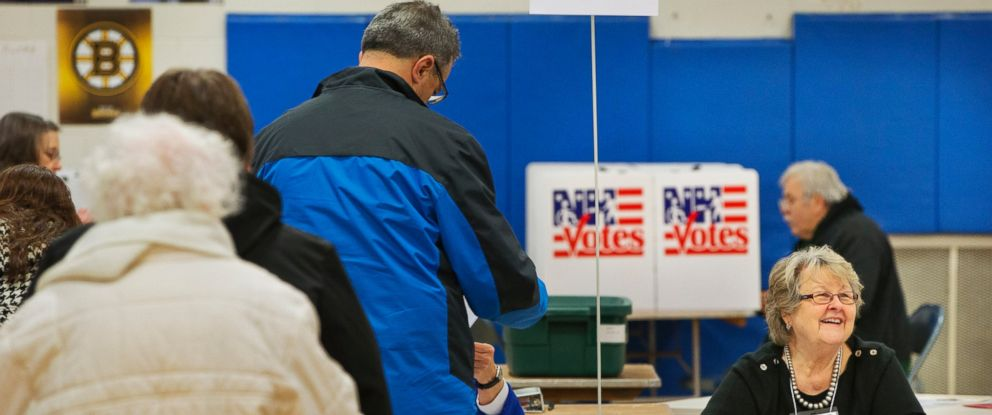 PHOTO: Brooks Thompson, right, checks voters in at a polling place at Broad Street Elementary in Nashua, N.H., Feb. 9, 2016, during the New Hampshire primary.