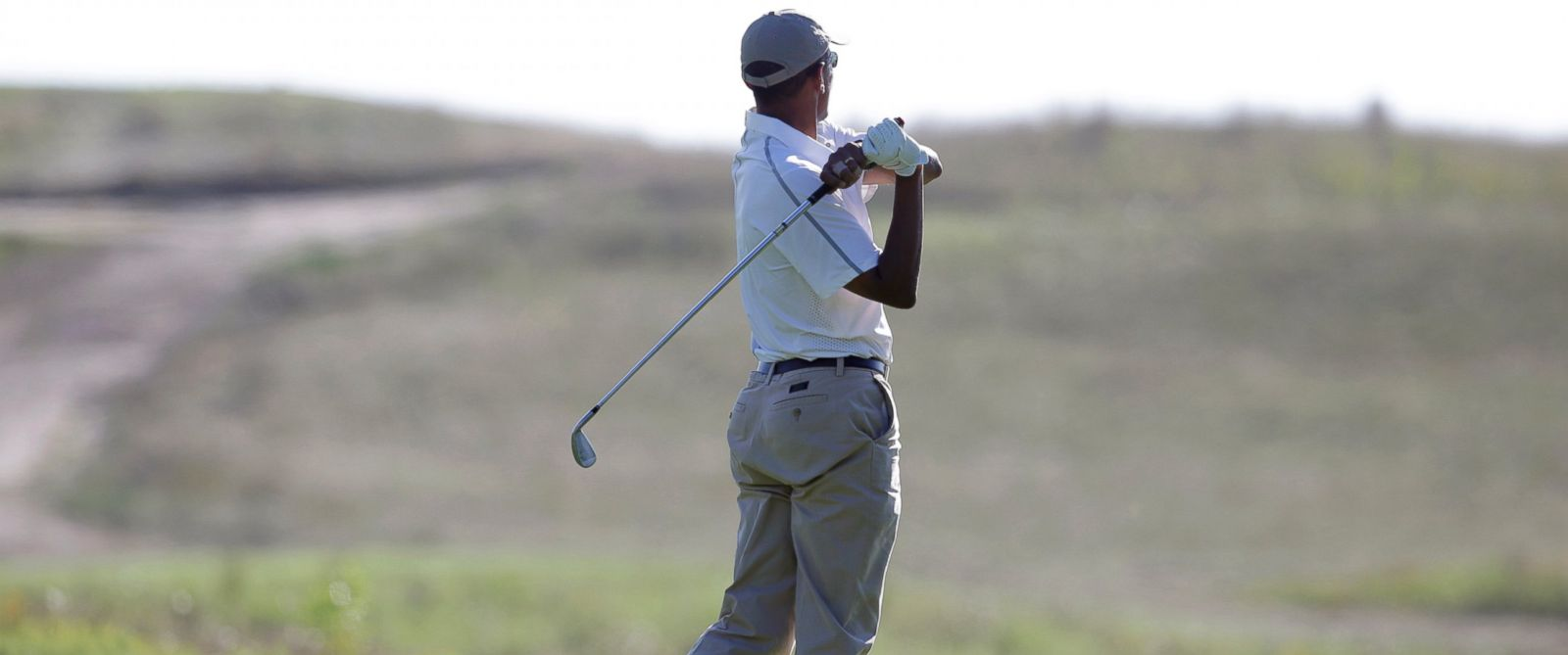 PHOTO: President Barack Obama follows through on a swing as he tees off while golfing at Vineyard Golf Club in Edgartown, Mass., on the island of Marthas Vineyard, Aug. 20, 2014.