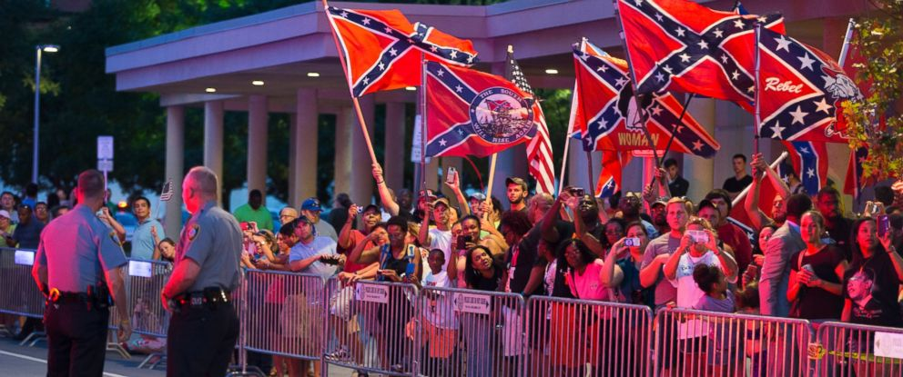 PHOTO: People wave Confederate flags outside the hotel that President Barack Obama is staying the night, July 15, 2015, in Oklahoma City.