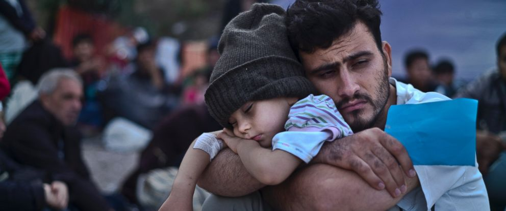 PHOTO: A Syrian refugee child sleeps in his fathers arms while waiting at a resting point to board a bus, after arriving on a dinghy from the Turkish coast to the northeastern Greek island of Lesbos, Oct. 4, 2015.