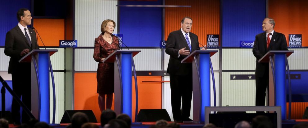 PHOTO: Mike Huckabee speaks as Rick Santorum, left, Carly Fiorina and Jim Gilmore listen during a Republican presidential primary debate, Jan. 28, 2016, in Des Moines, Iowa.