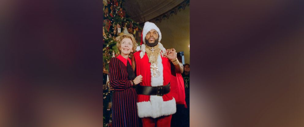 "PHOTO: Mr. T, of the television show the ""A-Team,"" poses as Santa Claus to help First Lady Nancy Reagan unveil the White House Christmas decorations on Dec. 12, 1983 in Washington."