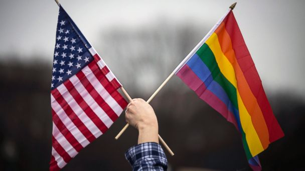 PHOTO: A participant holds both the U.S. national flag (L) and the LGBT community's symbolic  Rainbow flag (R) as people arrive on the mall for the Million Woman March in Washington, D.C., Jan. 21, 2017.