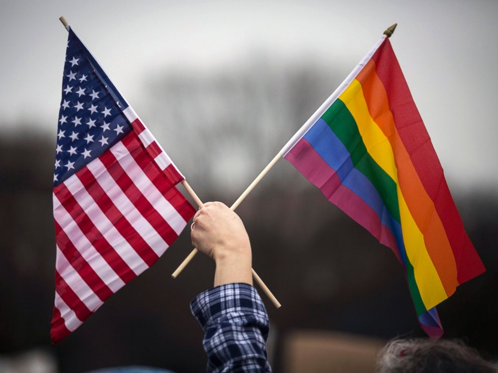 PHOTO: A participant holds both the U.S. national flag (L) and the LGBT communitys symbolic Rainbow flag (R) as people arrive on the mall for the Million Woman March in Washington, D.C., Jan. 21, 2017.