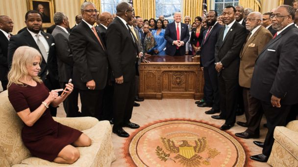 PHOTO: Counselor to the President Kellyanne Conway checks her phone after taking a photo as U.S. President Donald Trump and leaders of historically black universities and colleges pose for a group photo, Feb. 27, 2017, in Washington.