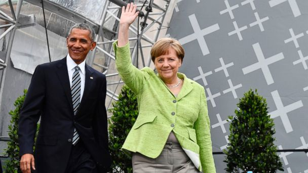 PHOTO: Former U.S. President Barack Obama and Chancellor Angela Merkel arrive on stage during the Protestant church day event at the Brandenburg Gate, on May 25, 2017, in Berlin.