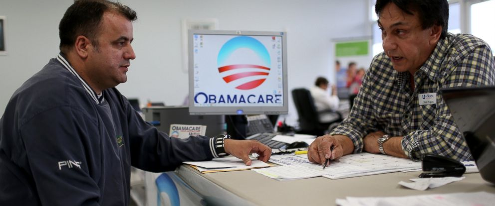 PHOTO: Ariel Fernandez (L) sits with Noel Nogues, an insurance advisor with UniVista Insurance company, as he signs up for the Affordable Care Act, also known as Obamacare, before the February 15th deadline, on Feb. 5, 2015, in Miami.