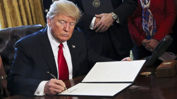 PHOTO: President Donald Trump signs Executive Orders in the Oval Office of the White House, including one to review the Dodd-Frank Wall Street to roll back financial regulations of the Obama era, Feb. 3, 2017, in Washington, DC.