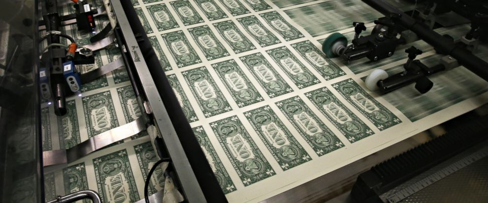 PHOTO: Sheets of one dollar bills run through the printing press at the Bureau of Engraving and Printing, March 24, 2015, in Washington, DC.