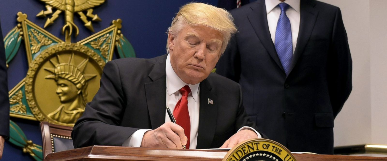 PHOTO: President Donald Trump signs an executive order alongside US Defense Secretary James Mattis and Vice President Mike Pence, Jan. 27, 2016 at the Pentagon in Washington.