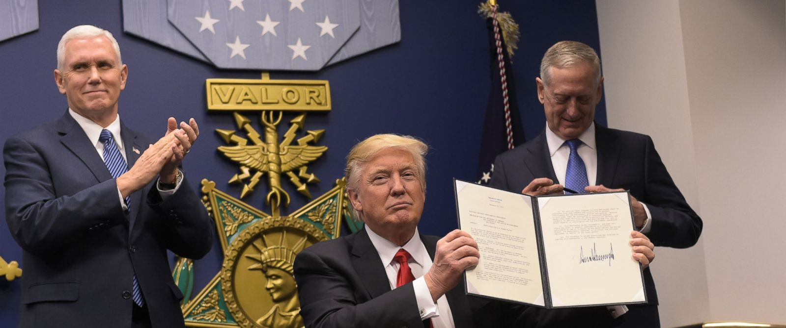 PHOTO: President Donald Trump shows his signature on executive orders alongside Defense Secretary James Mattis and Vice President Mike Pence, Jan. 27, 2016, at the Pentagon in Washington.