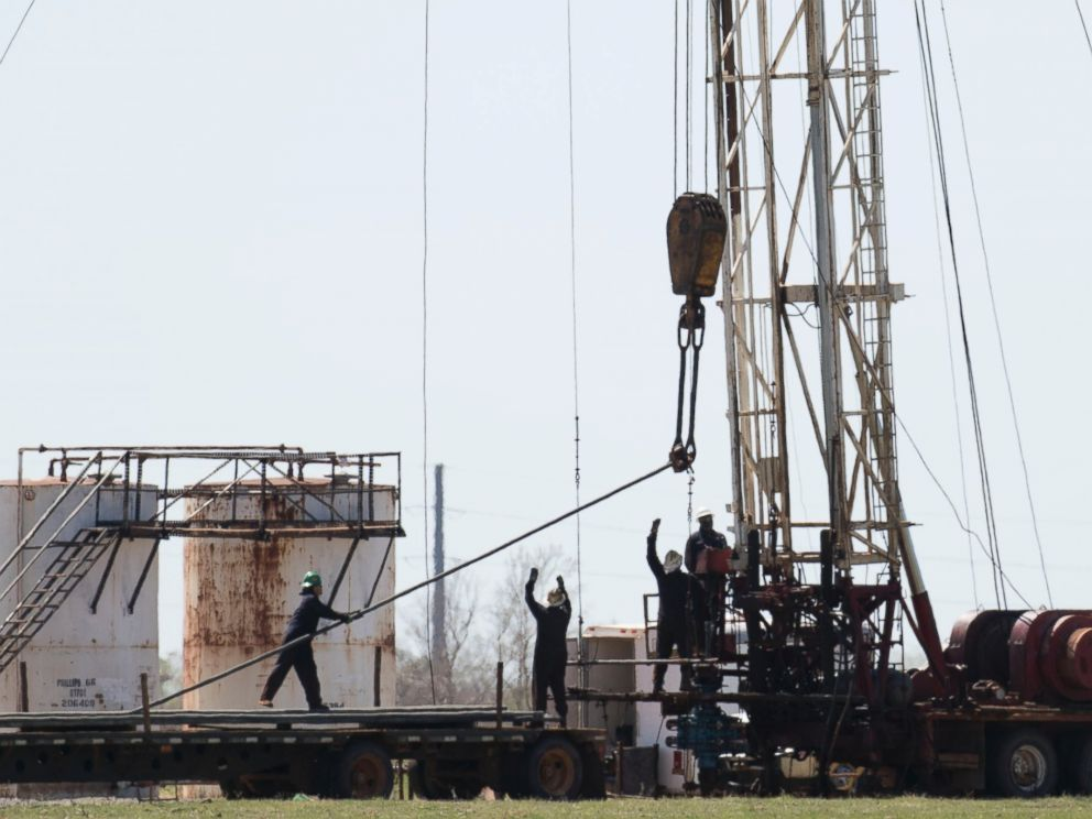 PHOTO: Oil field workers pull pipes from a fracking well, March 31, 2016, near, Crescent, Oklahoma.