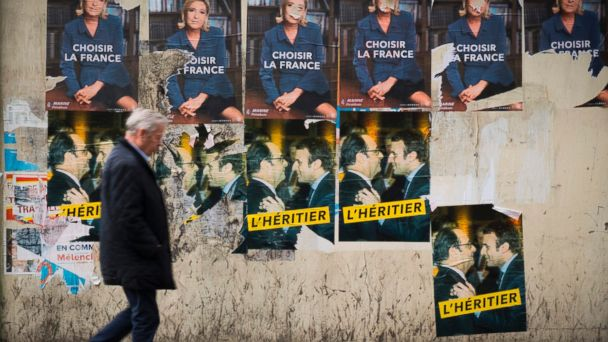 PHOTO: A man walks past vandalized campaign posters of French presidential election candidate Marine Le Pen and posters picturing French President Francois Hollande and French presidential election candidate, Emmanuel Macron, in Paris, May 5, 2017.