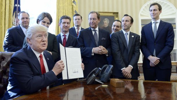 PHOTO: U.S. President Donald Trump flanked by business leaders signs executive order establishing regulatory reform officers and task forces in US agencies in the Oval Office of the White House, on Feb. 24, 2017, in Washington.