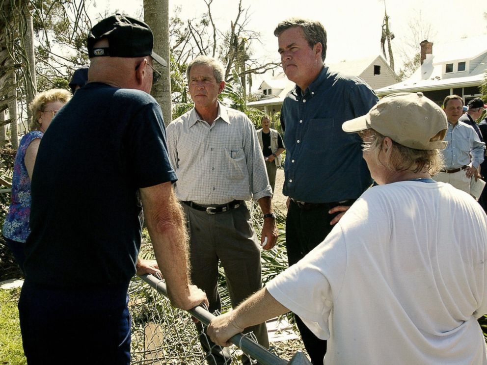 PHOTO: U.S. President George W. Bush (L) and his brother Florida Governor Jeb Bush (R) talk to local residents while touring the damage left by Hurricane Charley in Punta Gorda, Florida, on Aug. 15, 2004.