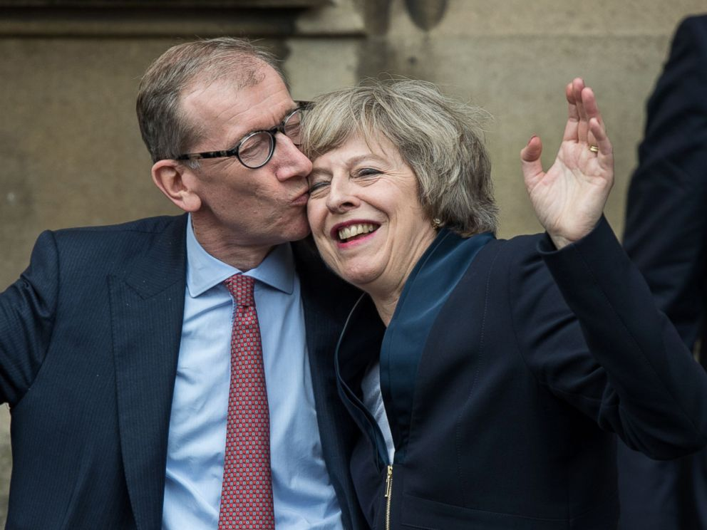 PHOTO: Theresa May receives a kiss from her husband Philip John May after speaking to members of the media at The St Stephens entrance to the Palace of Westminster in London, July 11, 2016.