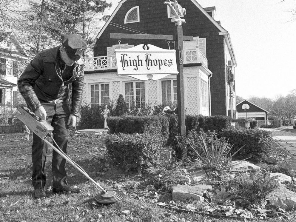 PHOTO: Suffolk County policeman uses mine detector as he sweeps through dead leaves on lawn of Ronald DeFeos 12-room, $75,000 Dutch colonial home in Amityville.