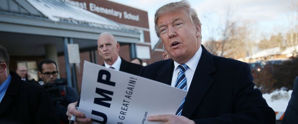 PHOTO: Republican presidential candidate Donald Trump prepares to autograph a campaign poster as he greets people as he visits a polling station as voters cast their primary day ballots on Feb. 9, 2016 in Manchester, N.H.