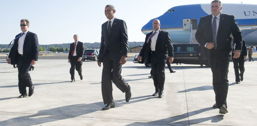 PHOTO: President Barack Obama, surrounded by Secret Service agents, walks across the tarmac as he arrives at Boeing Field in Seattle, July 24, 2012.