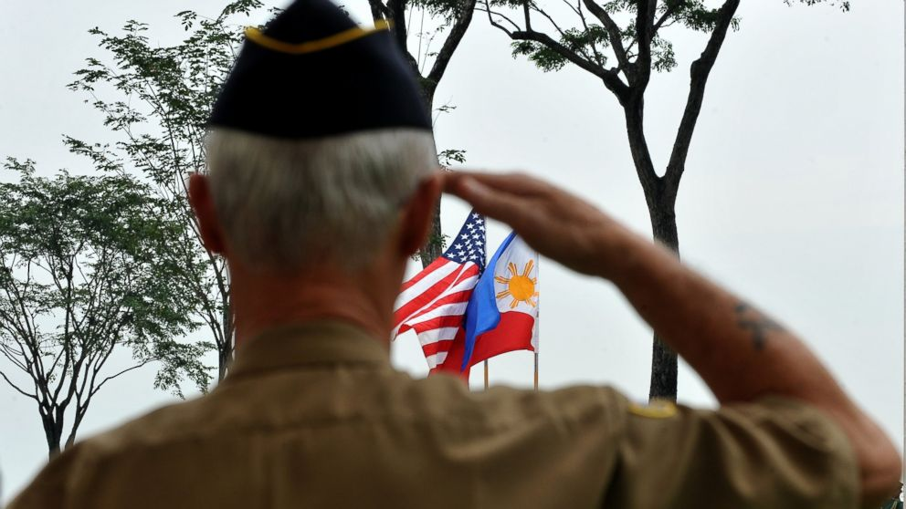 PHOTO: A retired American soldier salutes to the colors during Veter