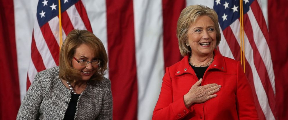 """PHOTO: Former Sen. Gabrielle Giffords, left, looks on as democratic presidential candidate former Secretary of State Hillary Clinton speaks during a """"get out the caucus"""" event at Iowa State University, Jan. 30, 2016 in Ames, Iowa."""